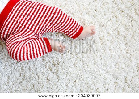 Close-up of baby body and legs in red Santa Clause trousers. New born child, little girl or boy. Kid having fun. Family, new life, childhood, holiday concept. Closeup for Christmas postcard