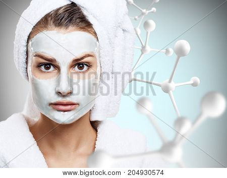 Beautiful woman with mask on face in big molecules chain over gray background. Innovation cosmetics concept.