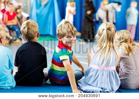 Children watching theater or concert at school. Little kid boy smiling. Kids from back, musical and theatrical performace