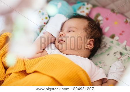 Sweet newborn baby girl is sleeping on her back in her crib, swaddled in yellow blanket.
