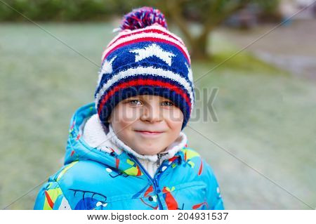 Portrait of happy cute little kid boy in colorful warm winter fashion clothes. Funny child having fun in winter forest or park on cold day.
