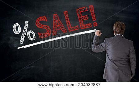 Businessman writes sale on blackboard concept picture