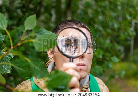 Image of botanist man with magnifying glass in summer forest