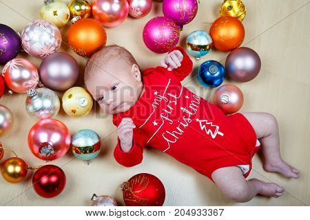 Adorable newborn baby with Christmas tree decoarations and colorful toys and balls. Closeup of cute child, little baby looking on decorated xmas tree Family, Xmas, birth, new life