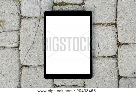 Tablet computer on grey stone background. Isolated white screen with copy space. Empty space for text. Empty blank screen.
