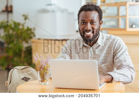 Inspiring ambience. Handsome cheerful man sitting at the table in a cafe and working on the laptop while smiling at the camera