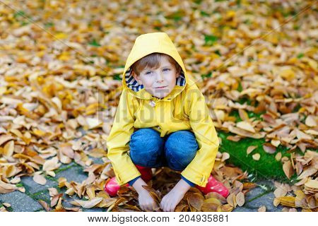 Portrait of happy cute little kid boy in yellow rain coat and red rubber boots with autumn leaves background. Funny child having fun and playing in fall forest or park on cold autumnal day.