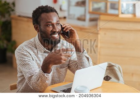 Pleasant discussion. Charming young man sitting at the table in the cafe and talking on the phone while smiling cheerfully