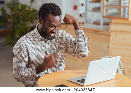Awesome news. Cheerful young man sitting at the table in coffee house hand raising hands in celebration, being happy about great news, having read email on laptop