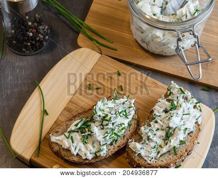 Home made bread on a wooden cutting board with curd cheese and ricotta and herbs. Decorated with green herbs
