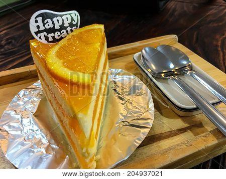 Orange cake on wood plate on a wood table