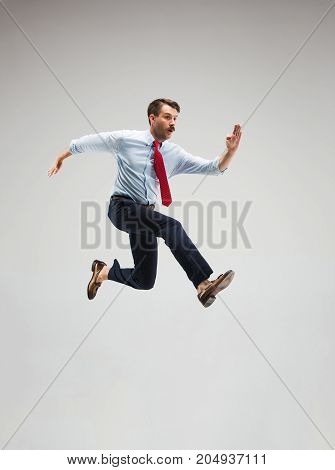 Businessman running on gray studio background. Concept of successful businessman