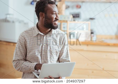 Looking for inspiration. Handsome young man sitting on the table in the cafe, holding a laptop and looking into the distance as if looking for inspiration