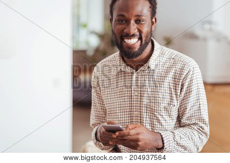 Mood-boosting conversations. Handsome cheerful man exchanging text messages with his friends and smiling happily at the camera