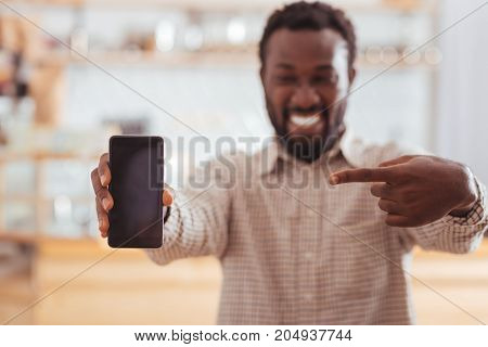 Happy about purchase. The focus being on the phone in the hands of a cheerful young man pointing at it with his finger while being happy about its purchase