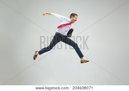 Businessman running with a briefcase, isolated on gray studio background