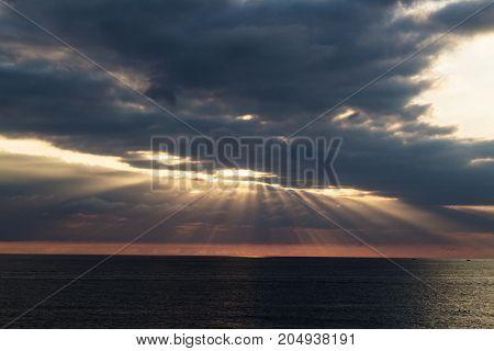 The ray of the sun makes its way through the clouds into the sea. Dramatic scene