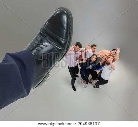 Scared and shocked team of young business men and women under boss pressure. Concept horror and fear of the boss. Collage with big shoe of boss