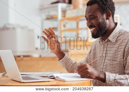 Hello there. Charming cheerful man sitting at the table in the coffee house, making some notes and greeting someone while making a video call