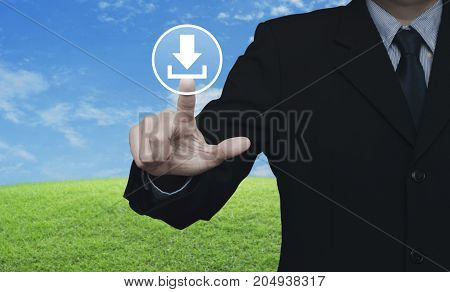 Businessman pressing download icon over green grass field with blue sky Business internet concept