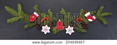 Christmas floral decoration with toys holly berry pine cones and winter greenery over chalkboard