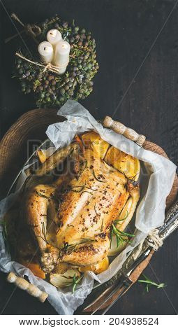 Christmas holiday table set with oven roasted whole chicken stuffed with oranges, bulgur and rosemary, decorative candles over dark wooden background. Top view, copy space, Slow food concept