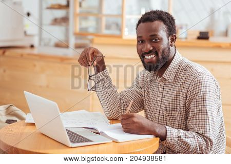Important information. Handsome cheerful man sitting at the table in the cafe and smiling at the camera while putting down crucial information into his notebook