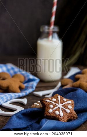 Homemade Christmas cookies and bottle of milk on blue napkin