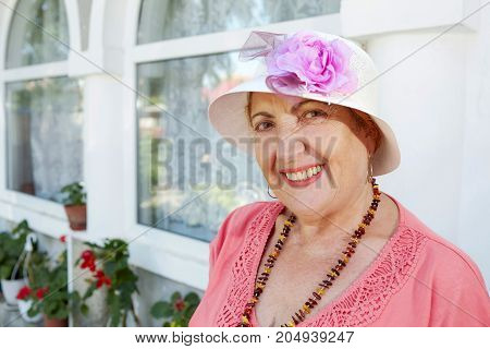 Portrait of a cheerful senior woman dressed retro style with beads and hat looking at the camera.