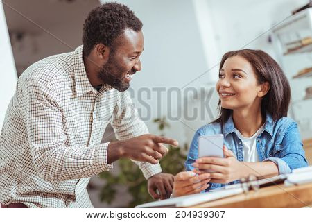 Lively discussion. Charming young man standing near his colleague, looking at social network posts and discussing them while laughing