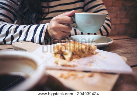 Closeup image of a woman holding and drinking hot latte coffee with a piece of raisin danish on wooden vintage table in coffee shop