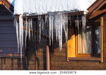Winter or spring background of bright icicles in the sunlight at the roof of snow covered wooden chalet