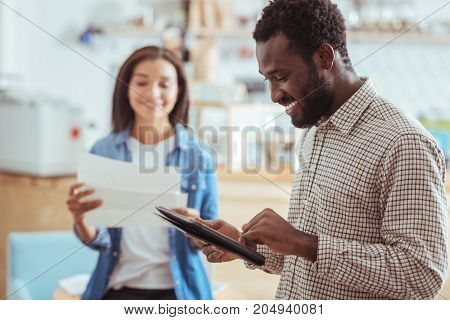 Preparing diligently. Handsome young man reading the speech notes from the tablet and his female colleague from the printouts while preparing for startup presentation