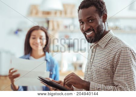 Careful revision. The focus being on a charming young man holding a tablet and revising his speech for startup presentation while his colleague looking through printouts in the background