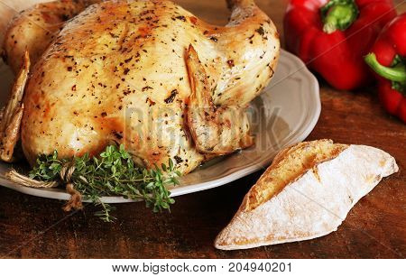 Whole roasted chicken with thyme, pepper and bread on wooden background .