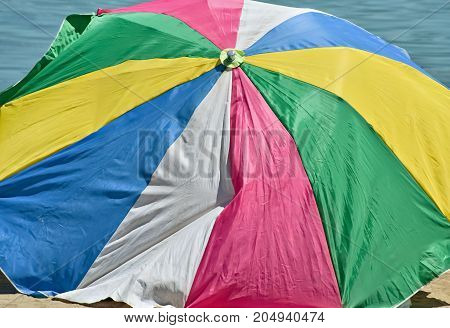 Closeup of a big colorful parasol on the beach