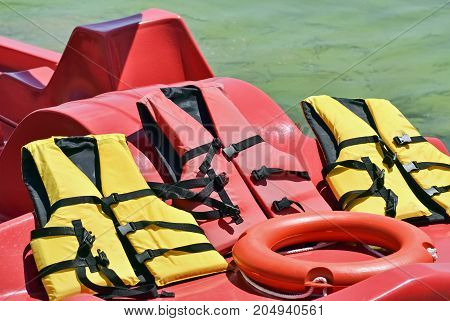 Several rubber jackets on a paddle boat and ring lifesaver