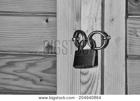 Closeup of the padlock on a wooden rustic door in black and white colors