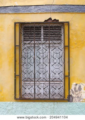 white wooden shuttered window behind wrought iron bars on a faded yellow peeling painted wall with rough patched of bare concrete and cracks with exposed brick