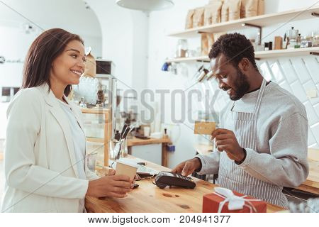 Quick service. Handsome pleasant barista holding his customers credit card and carrying out a payment procedure while the customer holding a cup of coffee and waiting for her card