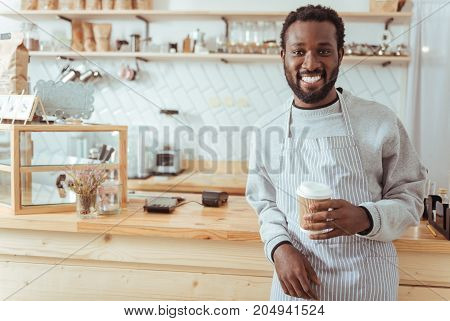 Worker of month. Handsome joyful young barista in an apron standing in front of the cafe counter and posing with a cup of coffee while smiling broadly