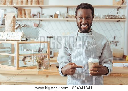 Best coffee. Handsome young male barista in an apron standing in front of a cafe counter and pointing at the cup of coffee in his hands while smiling at the camera