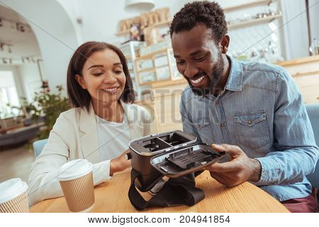 Childlike curiosity. Pleasant young man and woman sitting in the coffeehouse and examining the interior part of their new VR headset, having opened the front cover