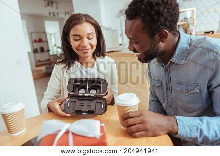 Satisfied interest. Pleasant pretty woman sitting at the table in the coffee house and showing her male friend the interior part of a VR headset