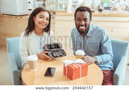 Nice purchase. Beautiful young woman and her pleasant female friend sitting in the coffeehouse and posing for the camera while holding a VR headset