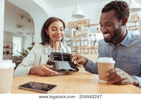 I can help. Charming young man sitting in the coffeehouse next to his best friend and removing a smartphone from a VR headset