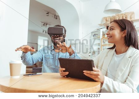 Interesting game. Joyful young woman sitting in the coffeehouse, holding a tablet and watching her best friend test a new VR headset