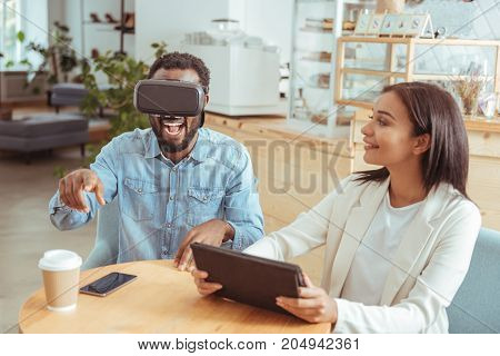 Best game. Charming young woman sitting in the cafe next to her best friend and watching him play with a new VR headset and be excited about it
