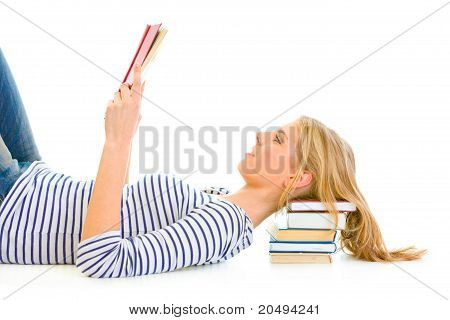 Lying on floor teengirl with resting head on pile of schoolbooks reading isolated on white