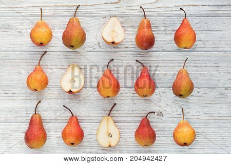 Abstract composition of fresh ripe organic pears on a white wooden background. Pattern of fruits. Food background. Autumn harvest concept. Flat lay.